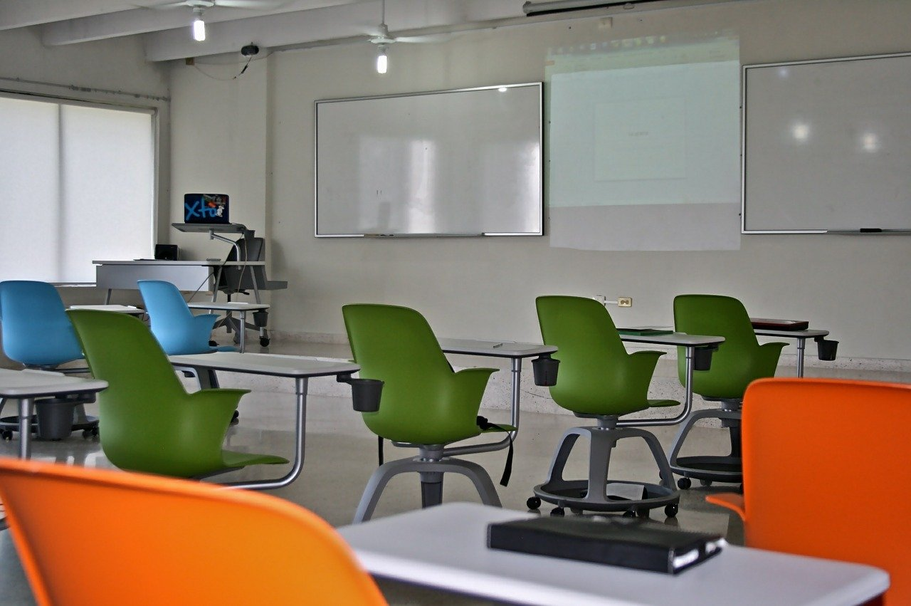 aula con sedie verdi azzurre e arancioni