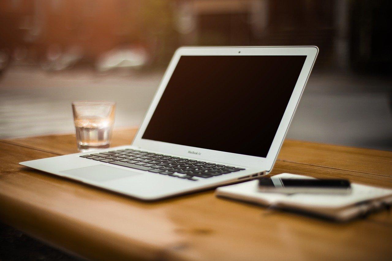 scrivania con pc, penne, notes, bicchiere