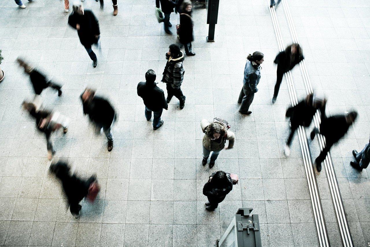 persone che camminano in un luogo pubblico preso dall'alto e sfocato