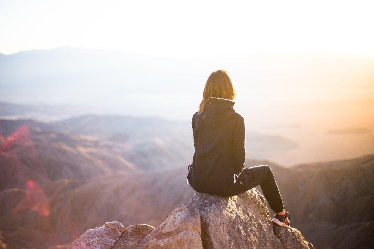 ragazza sulla cima di una montagna che guarda il panorama