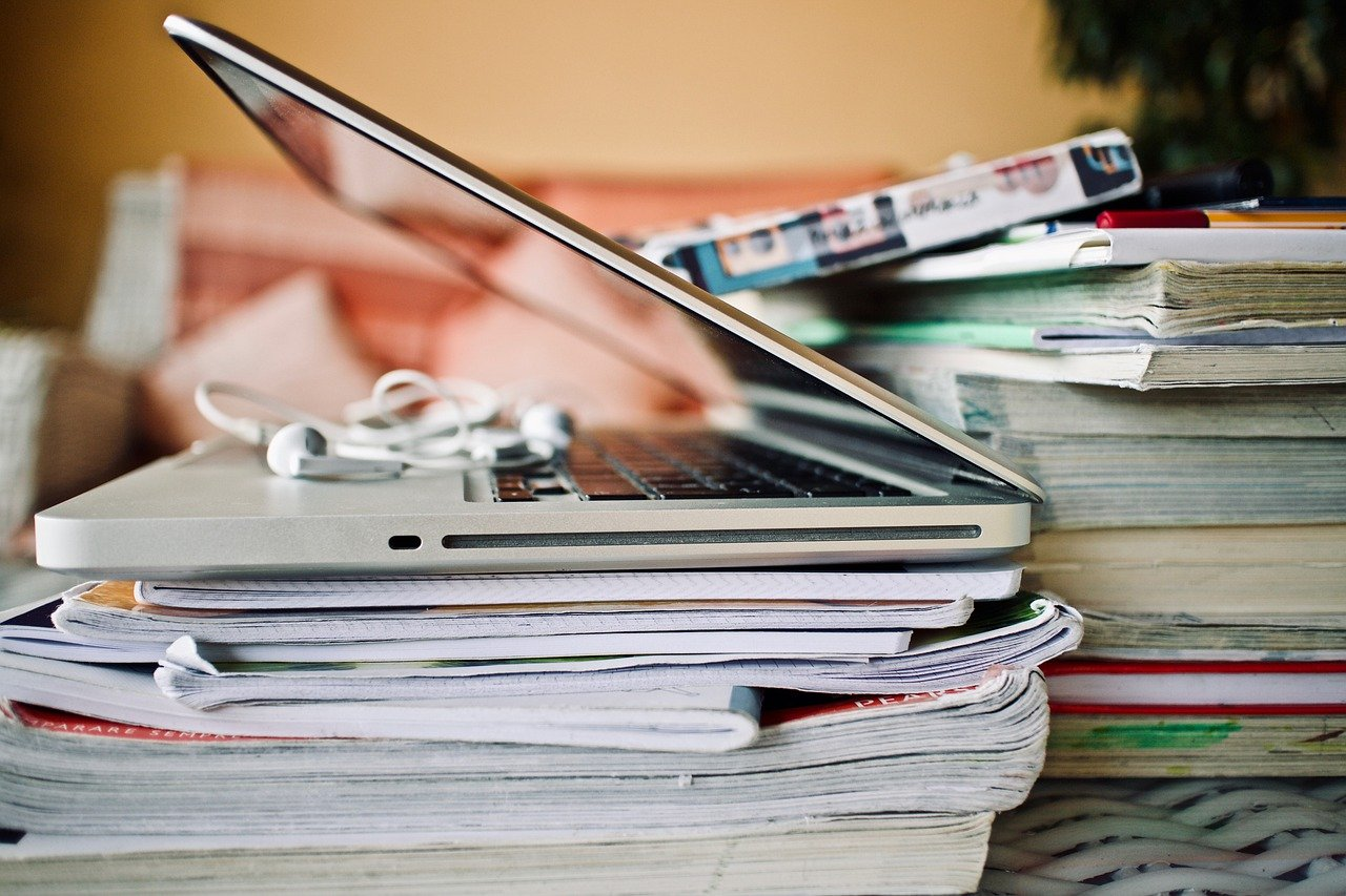 computer portatile, cuffie, quaderni, libri