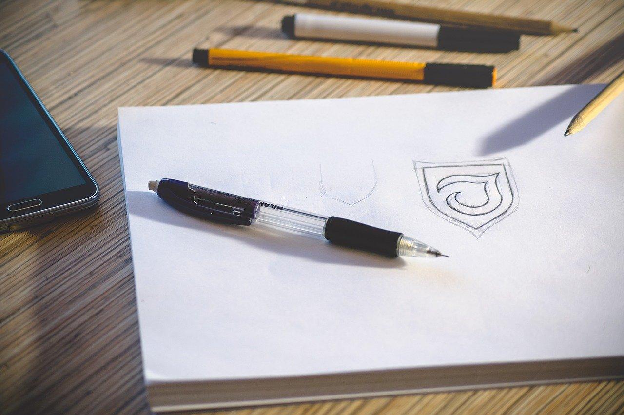 foglio bianco, penne e matite per disegnare logo