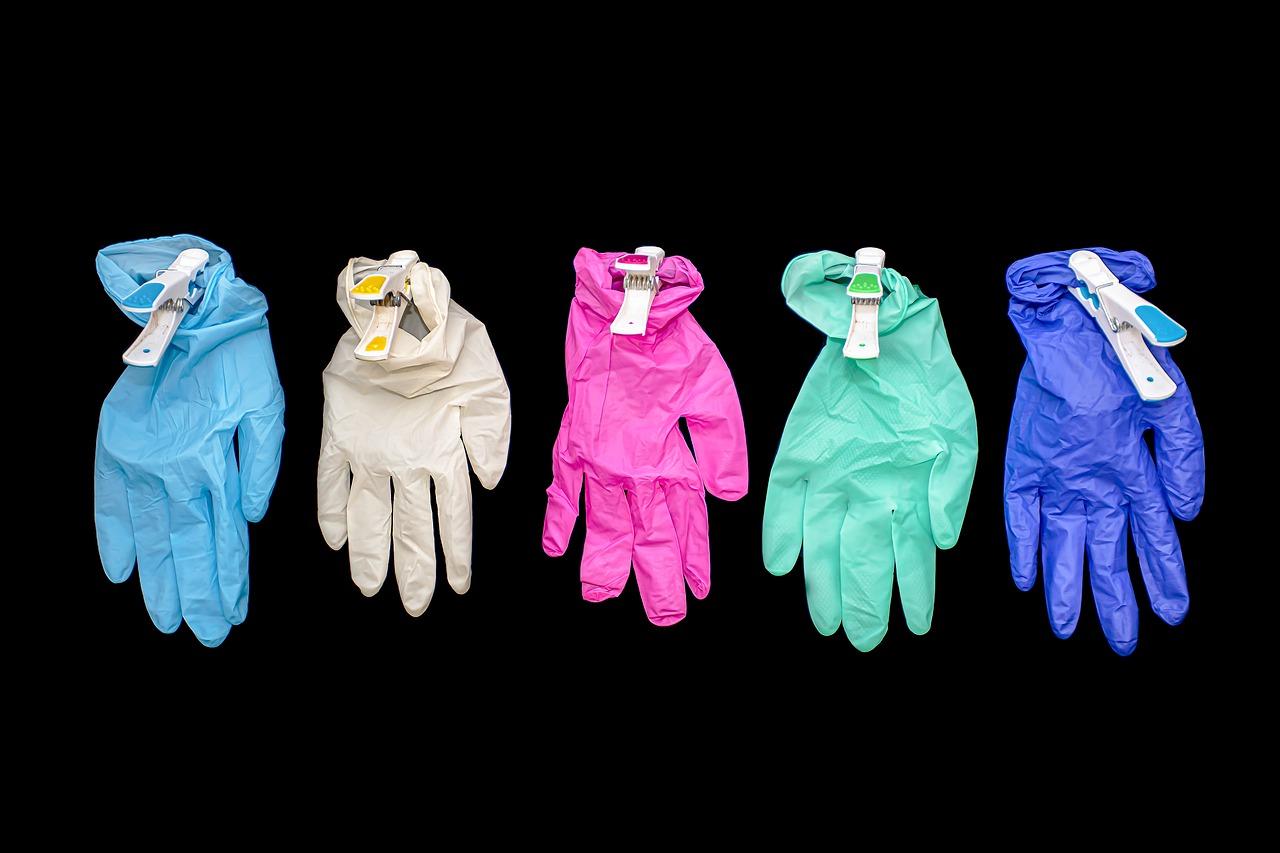 guanti colorati appesi con mollette su sfondo nero