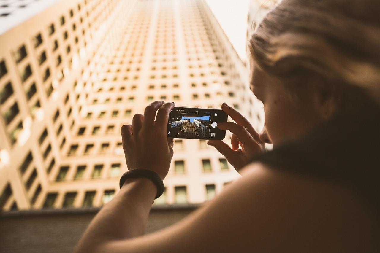 ragazza che fotografa edificio alto