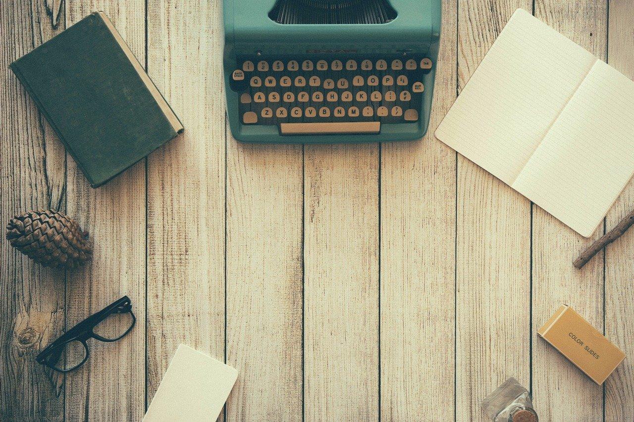 macchina da scrivere, quaderno, penna, occhiali