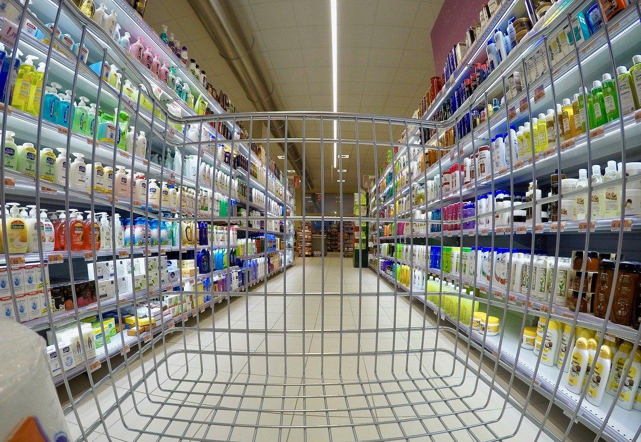 corsia di un supermercato vista attraverso le maglie di un carrello