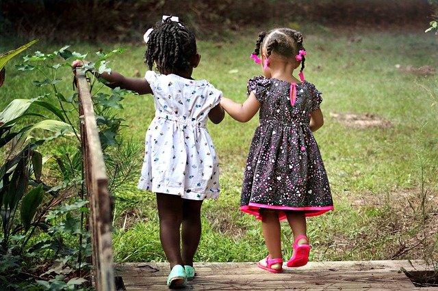 due bambine di spalle che si tengono per mano camminando