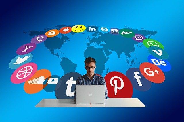 social media manager con computer e grafica con loghi dei social