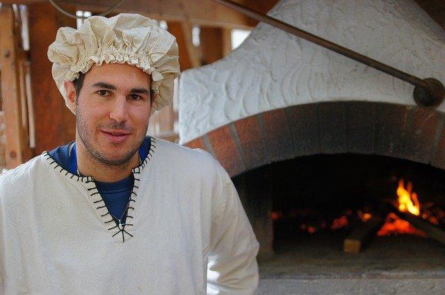 fornaio davanti al suo forno a legna