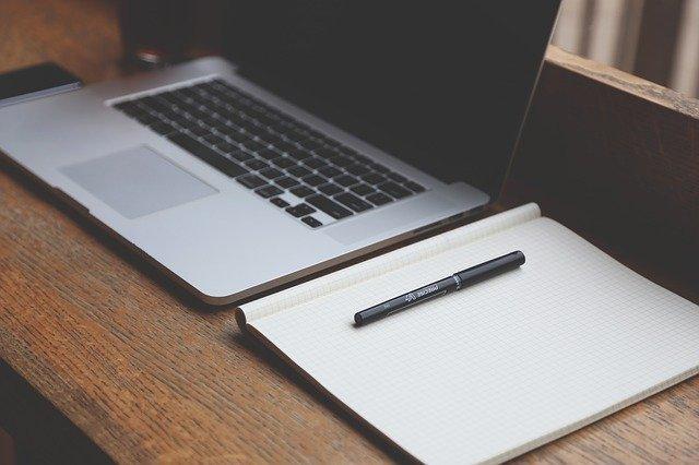 scrivania con computer e block notes
