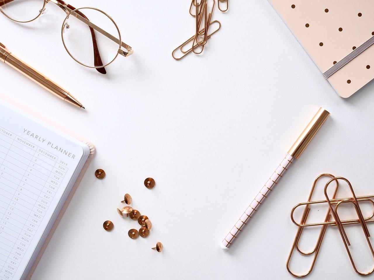 scrivania con puntine, graffette, agenda, occhiali