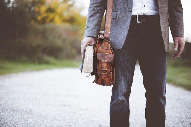 insegnante con borsa di pelle e libro in mano