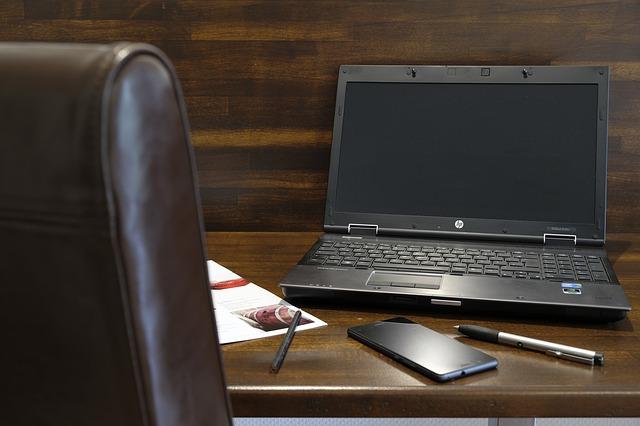 scrivania con sedia, computer, telefono, penne