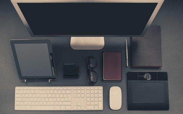 scrivania ufficio con schermo, tastiera, occhiali, agenda
