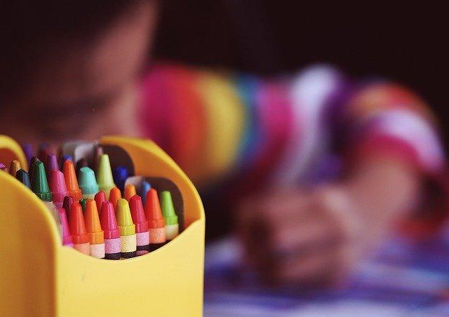 bambino che disegna con pennarelli colorati