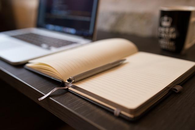 scrivania con computer e agenda