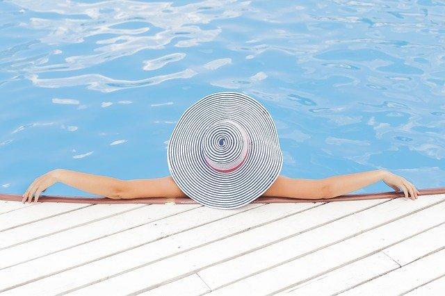 donna in piscina con cappello di paglia