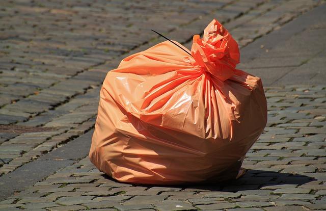 sacchetto rifiuti arancione su marciapiede